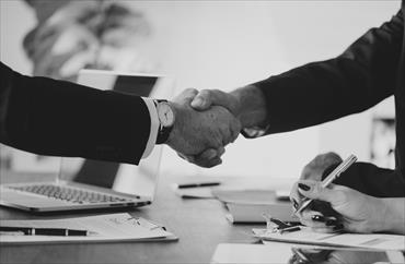 Image of two people shaking hands to confirm that an agreement has been reached