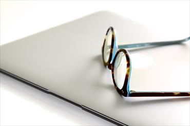 Image of a pair of glasses laying on top of a laptop